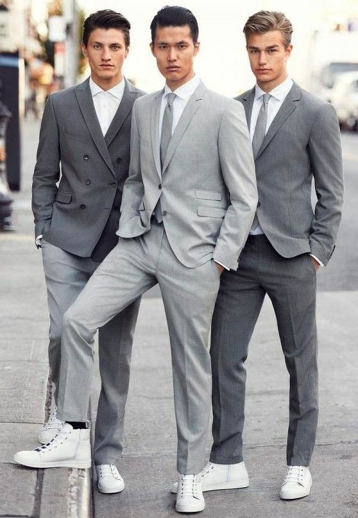 different shades of grey, worn by three young men, in smart two piece suits, all have white shirts and white sneakers, two of them are wearing ties