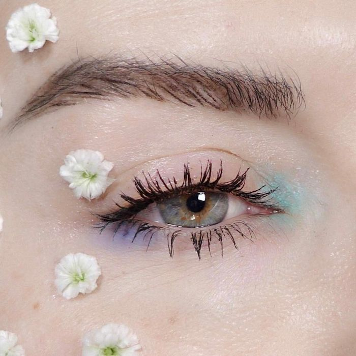daubs of teal and pale violet eyeshadow, on the corners of a blue eye, with black mascara, cute makeup looks, several small white and green blossoms surround the eye