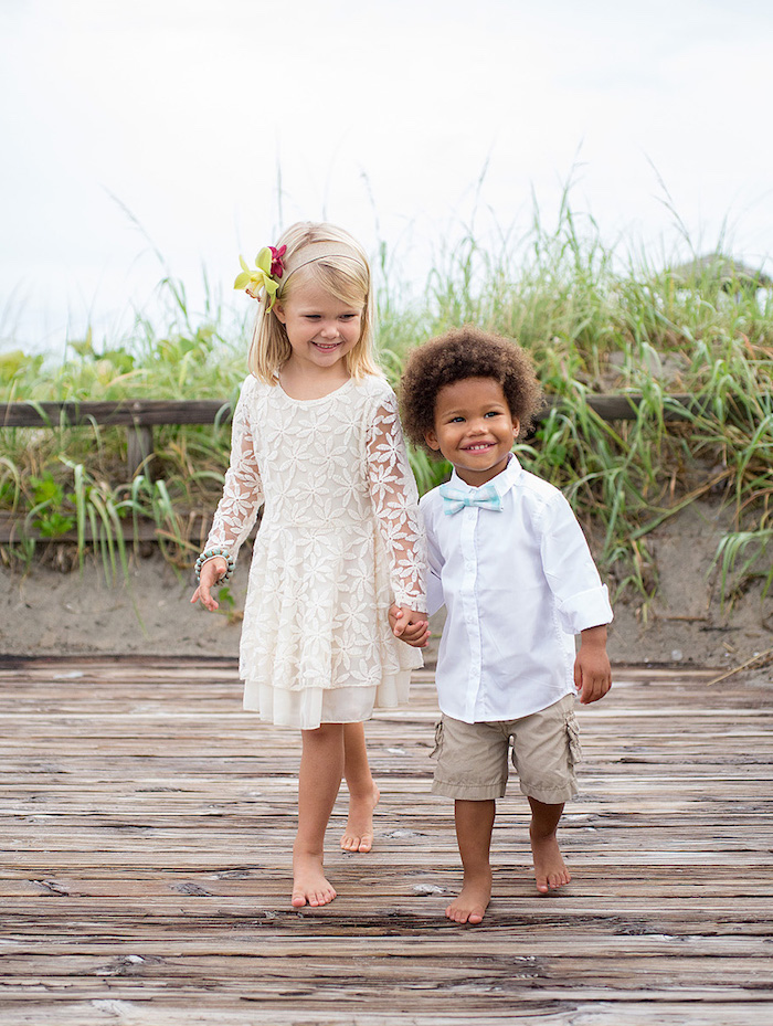 children holding hands and smiling, little boy in white shirt, khaki shorts and pale blue bowtie, little girl in a white embroidered dress, with flowers in her hair