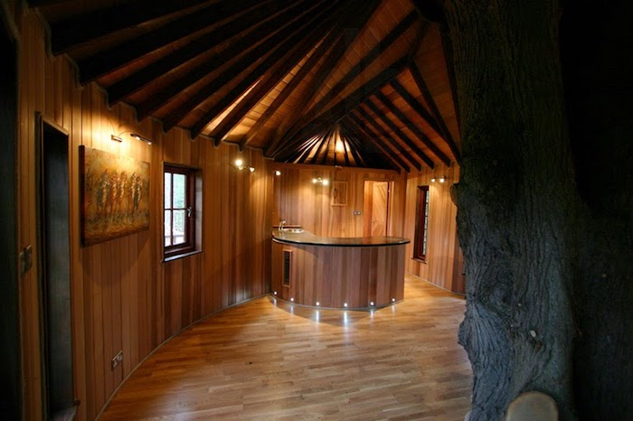 kitchen island and a framed artwork, inside a large oval room, with laminate floor, and wood panels on the walls, interior treehouse ideas,