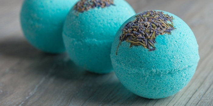 teal bath balls, three in total, topped with crushed dried lavender, and placed on a greyish-brown wooden surface