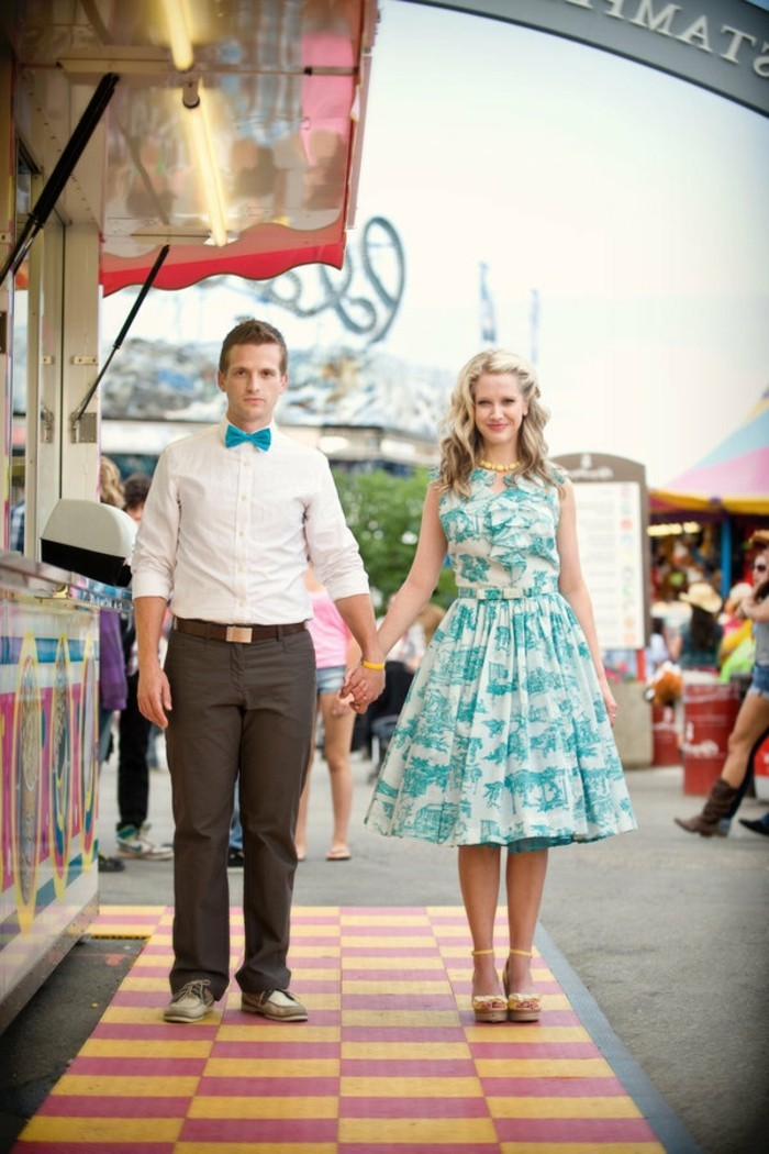 bowtie in turquoise, worn by man in white shirt, with beige trousers, holding the hand of a woman, with matching white and turquoise dress, mens wedding guest attire
