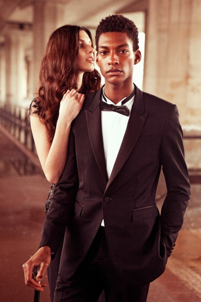 mens wedding guest attire, young black man, wearing a black tuxedo, with a white shirt, and a black bowtie, a cane in his hand