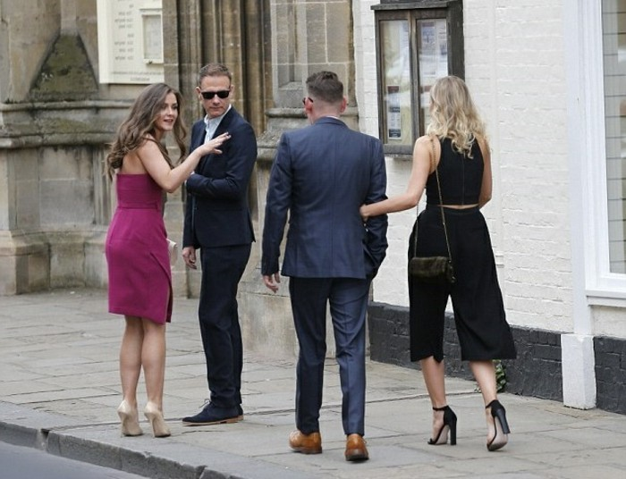 four people on a street, brunette woman in purple dress, blonde woman wearing black culottes and a top, and two men in dark suits, mens summer wedding attire, sunglasses and other accessories