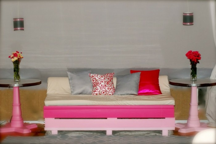 fuchsia and baby pink painted pallets, used to make a pallet couch, covered with soft light beige mattress, and several cushions