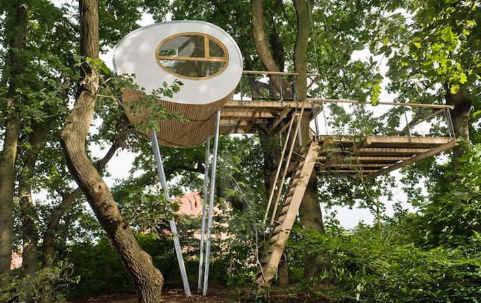rows of wooden stairs, leading up to an oval-shaped adult treehouse, in white and beige, built on tall metal rods,