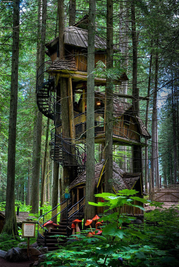 mushroom sculptures in red and cream, decorating a staircase, leading to a three story tree house, made of wood
