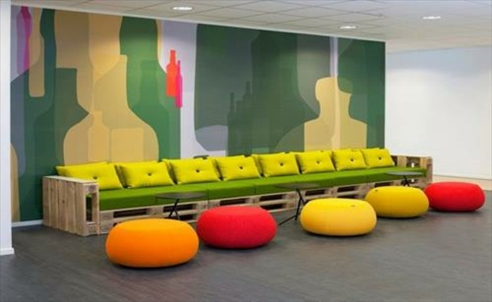 long bench or pallet couch, made from light wooden pallets, covered in green foam mattress, and decorated with vivid yellow cushions