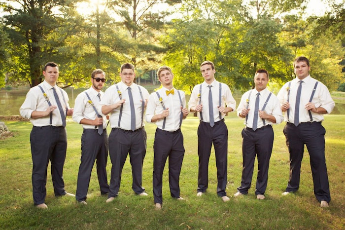 seven barefoot men, wearing identical outfits, black trousers and white shirts, with suspenders and grey neckties, one man is wearing a yellow bowtie, dressy casual men, standing in a garden with trees