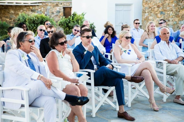people sitting on white garden chairs, mens wedding guest attire, formal suits in light and dark colors, white shirts and ties, women in summer dresses