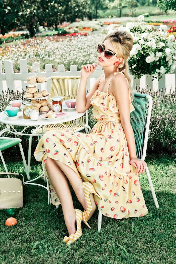 dressy casual, young woman with retro sunglasses, sitting near a small coffee table, with lots of pastries and tea cups, wearing yellow sundress, with ruffles and fruit print