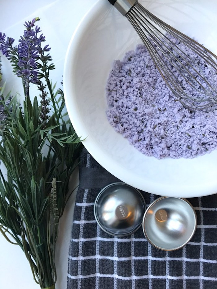 homemade bath bombs, coarse lumpy violet powder, inside a white ceramic bowl, with a whisking tool, metal moulding dish and several violet flowers