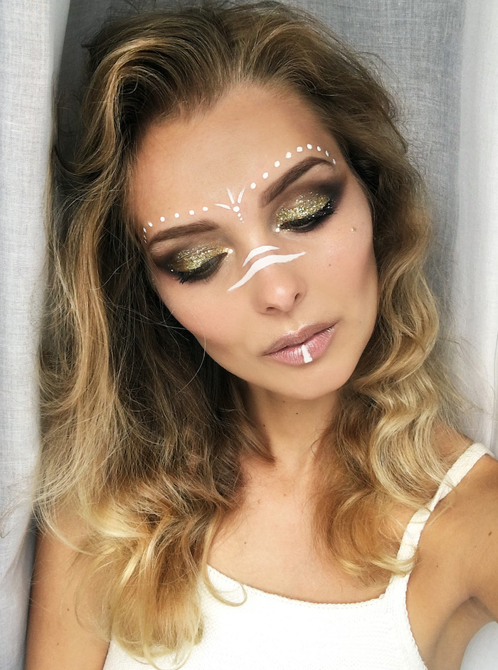 slim woman with wavy brunette hair, and blonde balayage, wearing brown and sparkly golden eyeshadow, makeup looks, glossy nude beige lipstick, and white face paint