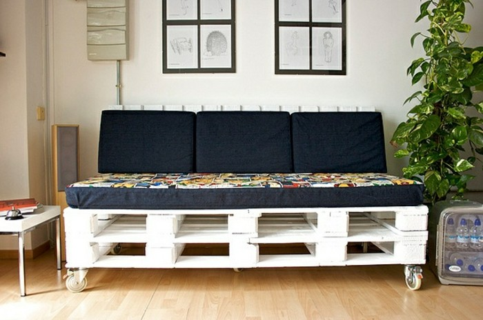 black cushions and cover on a foam mattress, decorating a pallet couch, made from several wooden pallets in white, with metal wheels