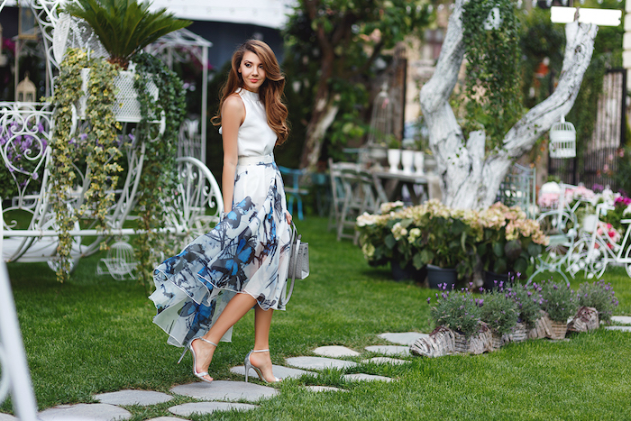 brunette woman with wavy hair, standing in a garden, wearing a floaty white asymmetrical dress, with blue butterflies print, garden party attire