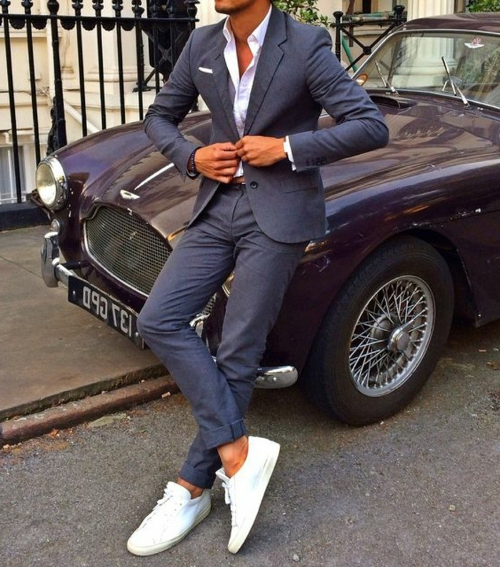 slim tan man, buttoning the jacket of his dark grey two-piece suit, and leaning on a vintage retro car, white shirt and sneakers