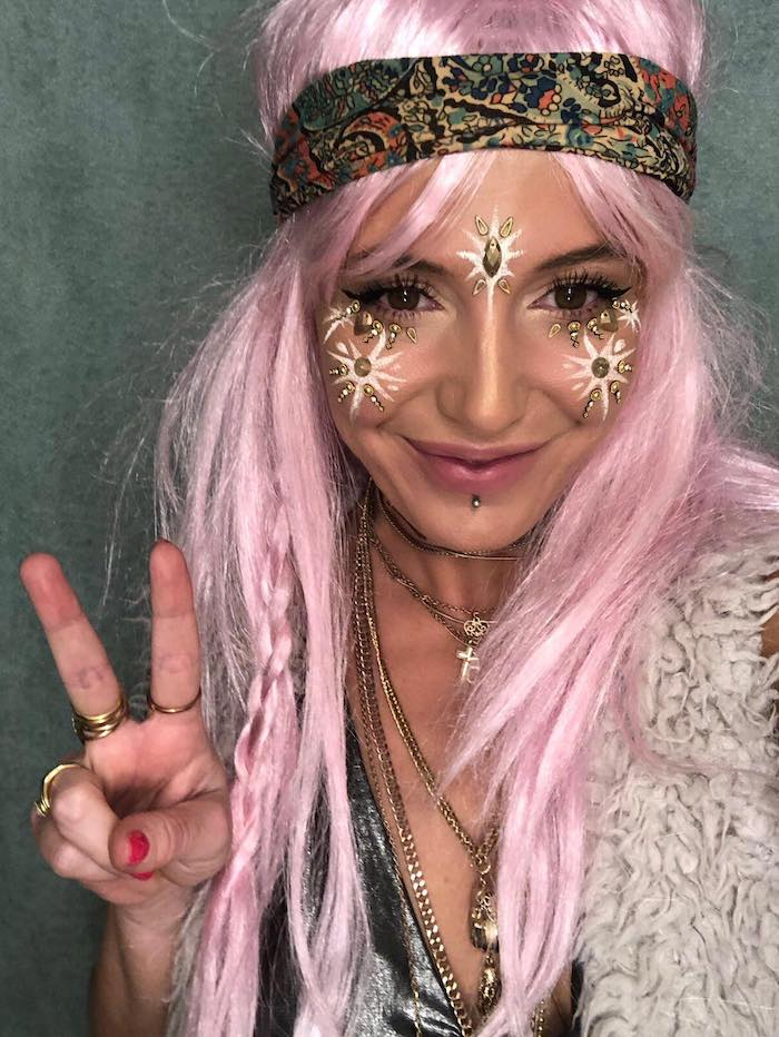 hippie costume with pastel pink long wig, decorated with small messy braid, and multicolored patterned headband, worn by smiling woman, with gold and white facepaint