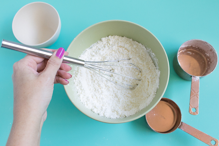 pink nail polish, on woman's hand, holding a whisking utensil, and mixing white powder, in a pale green plastic bowl, making bath bombs, white bowl and measuring spoons nearby
