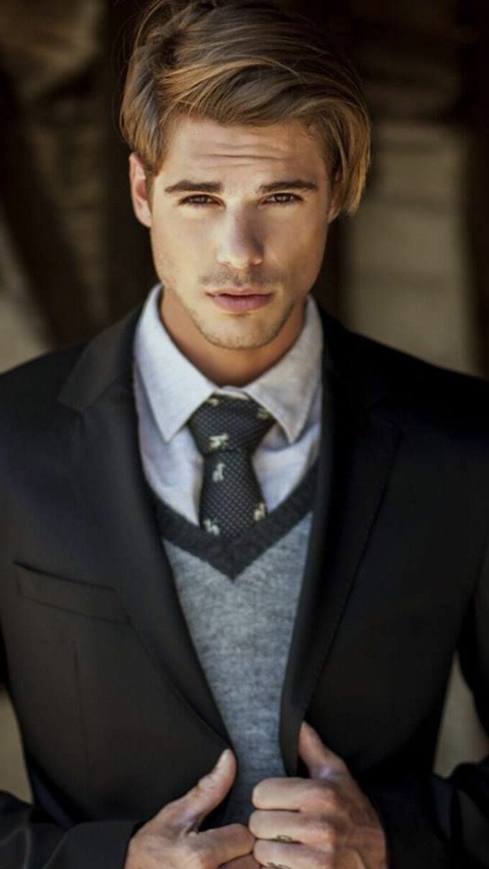 how to dress for a wedding male, blonde young man, wearing a grey woolen vest, over a pale grey shirt, and black patterned tie, smart black suit jacket