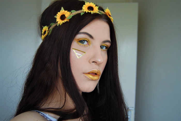 triangle drawn in gold paint, on the face of girl, wearing sparkly yellow lipstick, and eyeshadow in a matching color, dark long hair, flower wreath with artificial miniature sunflowers