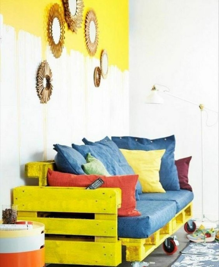 vivid yellow couch, made from painted pallets, affixed together and with added wheels, how to make pallet furniture, decorated with pillows in denim blue, red and yellow
