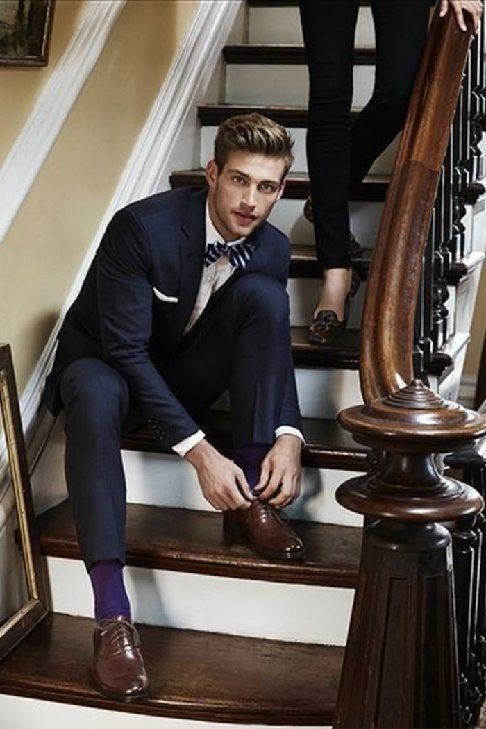 tying his shoelaces, black tie optional wedding, man in black suit, with white shirt, and a striped bowtie, brown leather shoes, and dark purple socks
