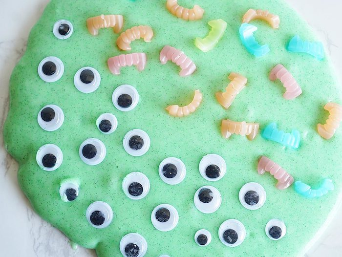 eye stickers in black and white, and tiny plastic vampire fangs, in different pastel colors, decorating a pile of smooth, foamy green slime