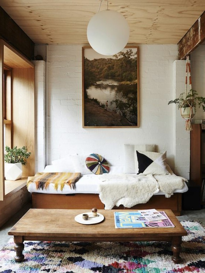 multicolored textured rug, inside a small living room, wooden settee covered in throws and blankets, simple living room designs, low vintage coffee table