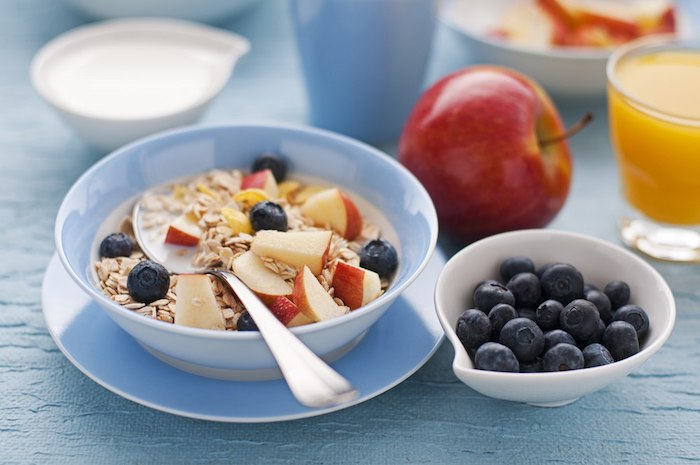whole apple and a glass of orange juice, near a bowl containing a spoon and rolled oats, apple chunks and blueberries