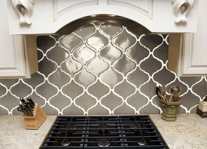 glossy creamy grey arabesque tile backsplash, with white joints, near a spotty beige counter top, with an inbuilt black hob