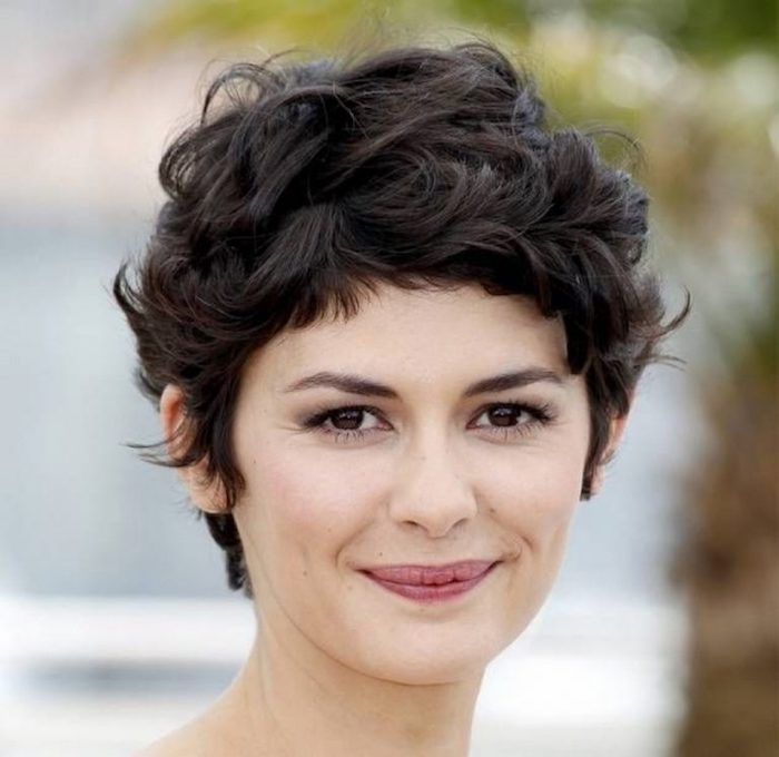 short haircuts for curly hair, audrey tautou smiling with a wavy, dark brunette pixie cut, seen in close up, with discrete make up
