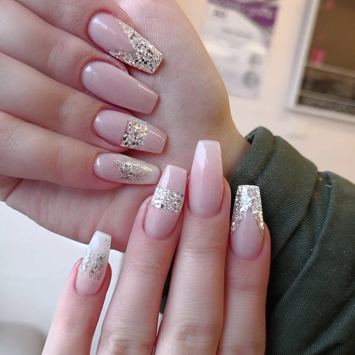 smudges and stripes, and geometric figures, created with silver glitter, decorating the baby pink manicure of two hands, coffin shaped nails