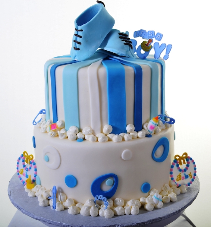 sugar pearls and decorations, made from blue and white fondant, pair of small shoes, stripes and oval shapes, on a two-layered cake, baby shower cakes for boys