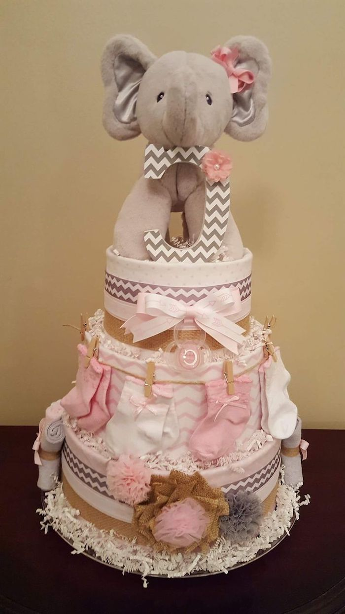 beige stuffed elephant toy, placed on top of a nappy cake, decorated with pale pink ribbons, little socks and tulle bows
