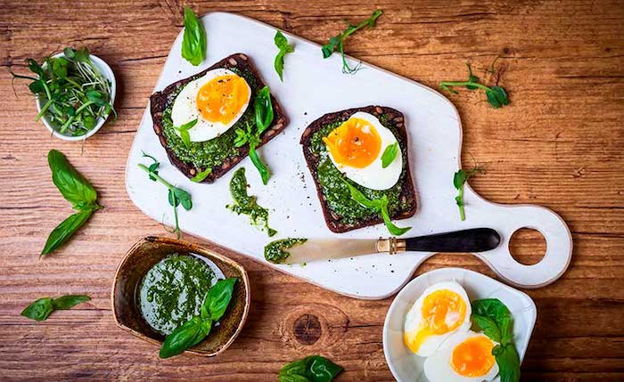 spread made from spinach, on two pieces of toasted bread, garnished with halves of boiled egg, and placed on a white cutting board