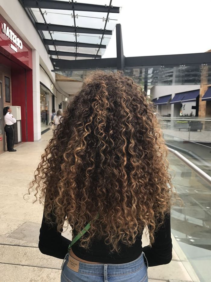 highlights in light blonde, on brunette hair, long curly hairstyles, seen from the back, girl in black jumper, and blue jeans