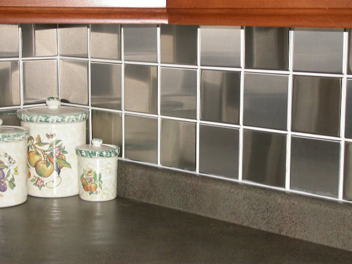 corner of a kitchen, covered in glossy and reflective, square dark grey tiles, with white joints, smooth dark grey counter top, with three colorful containers