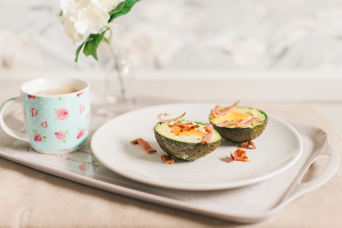 avocado cut in two halves, with egg and bacon flakes, on a white round plate, breakfast menu ideas, cup of milk tea or coffee next to it