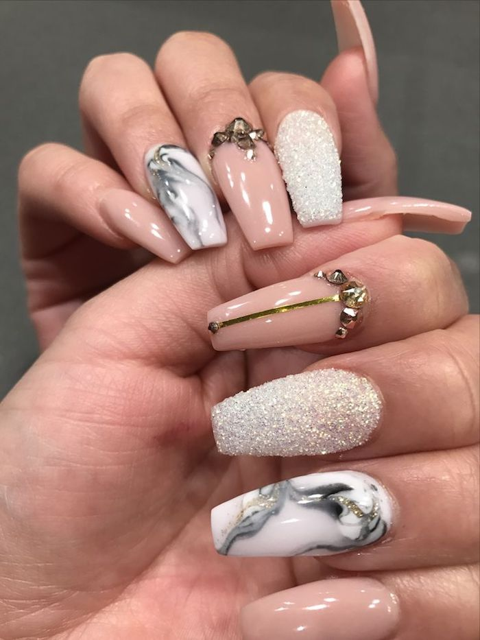 rhinestones in gold and white textured glitter, decorating the coffin shaped nails, of two hands, pale nude pink nail polish, and white nail polish decorated with grey, marble-like patterns