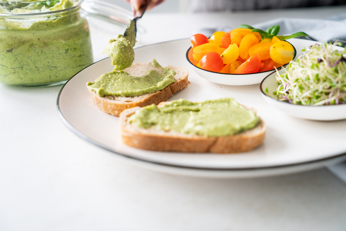 cherry tomatoes in a bowl, basil pesto with avocado, spread on two bread slices, placed on white plate