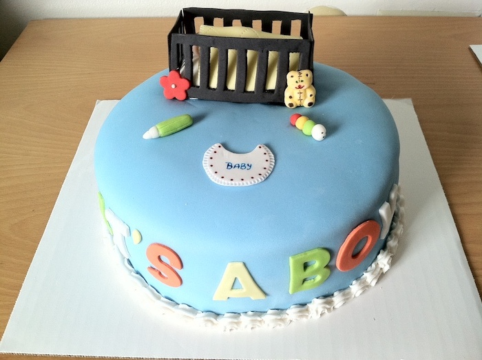 crib in dark brown, made from fondant, with a yellow blanket, a teddy bear and other baby items, on a cake with smooth blue frosting, baby shower cakes for boys, decorated with the words it's a boy