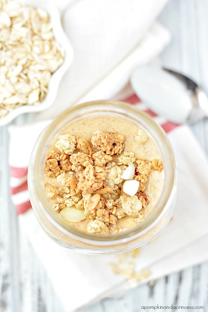 granola and nuts, strewn on top of a pale orange porridge, inside a glass jar, simple breakfast ideas, small bowl with rolled oats, and metal spoon nearby