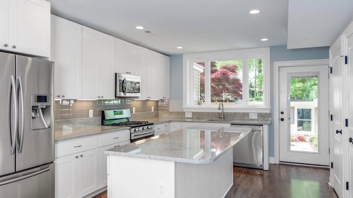 fridge in a metallic silver color, near a beige subway tile kitchen backsplash, white cabinets and glossy, marble counter tops