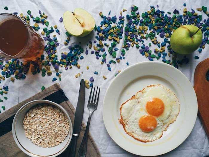 sunny side up eggs, two on a white round plate, near a bowl with rolled oats, and a jug of dark yellow juice, healthy low calorie breakfast, green apples and cutlery