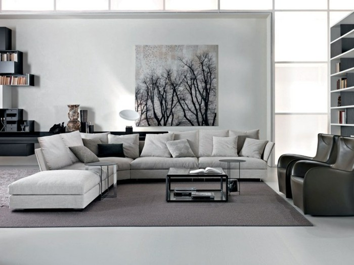 large pale grey corner sofa, and a black coffee table, inside a spacious room, with white walls, how to decorate a living room, two black leather armchairs