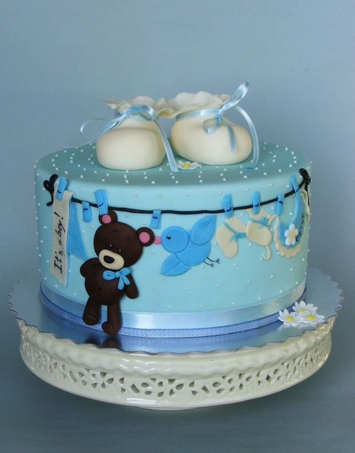 clothes line with a brown teddy bear, little white shoes, a baby's bib, and other items, decorating a pale blue cake, topped with a pair of white baby booties, with pale blue ribbons