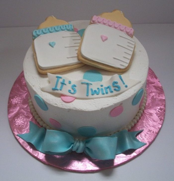 it's twins written in blue frosting, on a white fondant ribbon, decorating a white cake, twin baby shower cakes, topped with two cookies, shaped like baby bottles