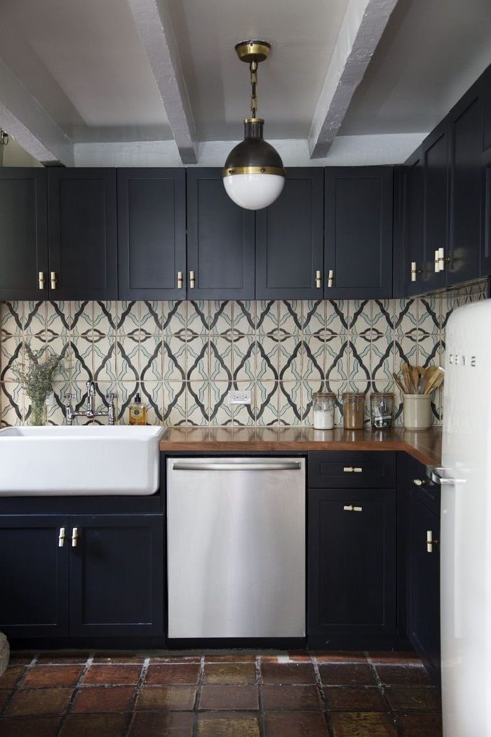 patterned tiles in cream, grey and pale blue, arabesque backsplash design, on the walls of a kitchen, with dark brown, natural stone floor, and black cabinets