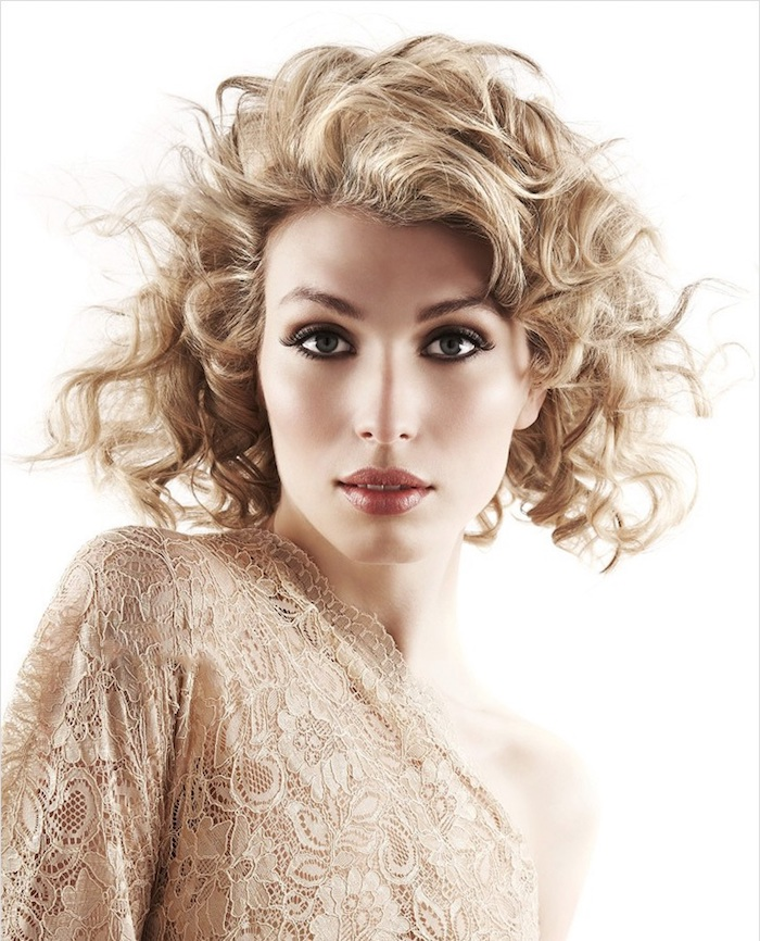 lace one-shouldered dress in beige, worn by woman with smokey eye make up, and brownish glossy lipstick, windswept ash blonde hair, hairstyles for short curly hair