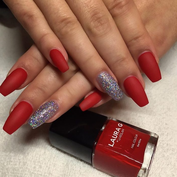 red matte nail polish, on medium long oval-shaped nails, with square tips, attached to a pair of tan hands, resting near a bottle of red nail polish